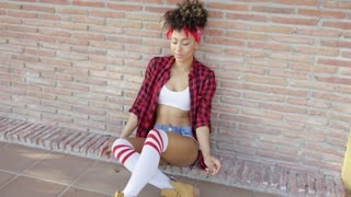 Fashionable sexy african american girl sitting on urban street. She wearing skimpy denim jeans high knee socks and checkered red shirt. She leaning against brick wall.