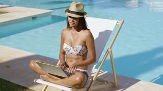 Fashionable young woman relaxing at the pool sitting cross-legged in a bikini and trendy hat on a deck chair working on a laptop