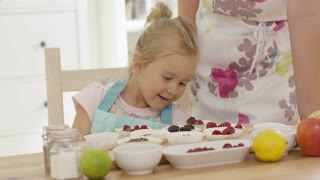 Female child in blue overalls placing little berries on muffins for baking as unidentifiable woman leans on table