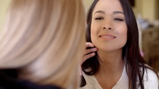 Female cosmetician working with client