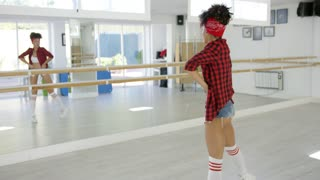 Female dancer practices her moves in studio before a wall covered in mirror panels