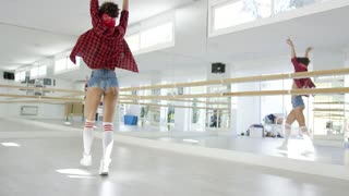 Female dancing student takes steps in brightly lit studio in front of mirrored wall