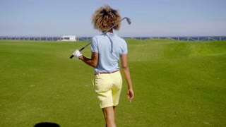 Female golfer walking down a fairway