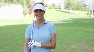 Female golfer wearing visor and blue polo shirt smiles at camera while standing on golf course