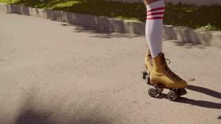 Female Legs On Vintage Roller Skater On The Road.
