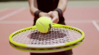 Female tennis player balancing a neon yellow tennis ball on her racket in a close up view with focus to the ball