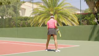 Female tennis player preparing to serve