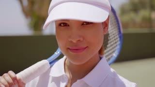 Female Tennis Player with Racket Wearing Sun Visor