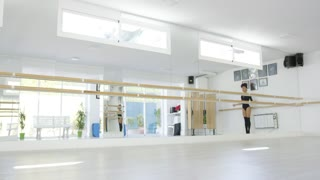 Fit athletic young dancer leaping in the air as she practices in a dance studio in front of a large wall mirror low angle with copy space.