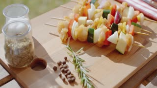Four chicken and vegetable kabobs on cutting board