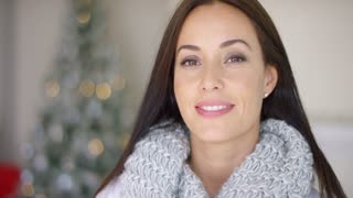Friendly young woman in a soft grey winter scarf celebrating Xmas at home in a festive living room with a decorated Christmas tree