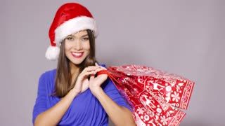 Friendly young woman wearing a festive red Santa hat with Christmas shopping bags in her stands standing looking at the camera with a lovely smile on grey with copy space.