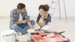 Frustrated handsome black couple talking beside bucket of paint and ladder
