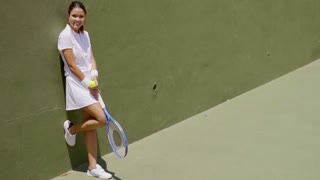 Full Length Portrait of Smiling Attractive Young Brunette Woman Wearing White Tennis Outfit and Holding Racket While Leaning Against Wall on Sunny Outdoor Court