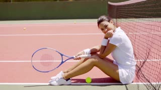 Full Length Profile Portrait of Smiling Attractive Young Brunette Woman Wearing White Tennis Outfit Sitting on Ground Near Net with Racket and Ball on Sunny Outdoor Court.