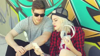 Fun young hipster couple listening to music on a mobile phone as they sit on the street in front of a colorful graffiti covered wall