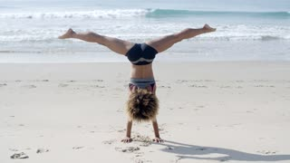 Girl Doing A Handstand On A Beach