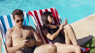 Girl grab and thow away mobile phones from her and her boyfriend and start real life. They lying on sun beds next to the swimming pool in the middle of summer.