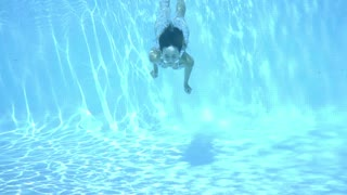 Girl swimming underwater in a swimming pool through sparkling sunlit water towards the camera in an active lifestyle concept