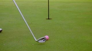Golfer preparing to sink a putt
