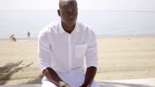 Good looking black model seated near sandy beach