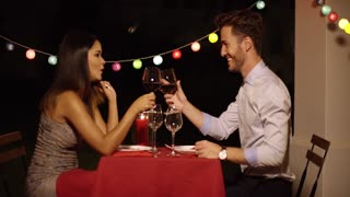 Good looking couple toasts with glasses of wine across red covered dinner table in restaurant