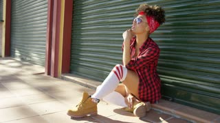 Gorgeous african american girl sitting next to urban tin fence. She wearing short skimpy jeand haeavy work boots and checkered shirt. Bandana on her head.