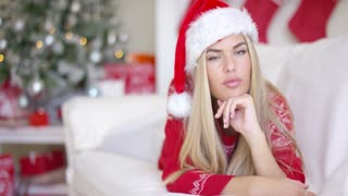 Gorgeous blond young woman lying on couch dressed in Santa Claus hat and red winter woolen sweater at Christmas time. With tree behind her back. She looking at camera