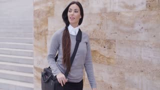 Gorgeous business woman walking past wall