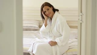 Gorgeous female adult in white bath robe sitting on bed and adjusting hair while framed by doorway in hotel room