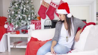Gorgeous friendly young woman celebrating Christmas at home in a festive red Santa hat as she sits on a sofa in her living room