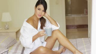 Gorgeous relaxed young woman drinking a mug of coffee as she spends a lazy day at home relaxing on her bed