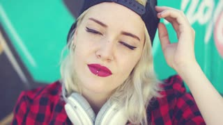 Gorgeous sexy young blond woman in a trendy baseball cap with a lower lip piercing and headphones around her neck looking dreamily at the camera