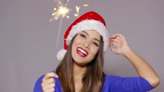 Gorgeous sexy young woman in a festive red Santa hat celebrating Christmas with a burning sparkler in her hand and a beaming smile