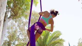 Gorgeous sporty supple young woman working out on a pair of purple silk ribbons hanging from a tree suspended midair in a graceful pose