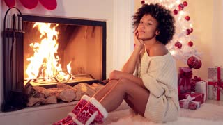 Gorgeous stylish young woman celebrating Christmas at home sitting on the floor in front of a roaring fire in festive red booties with the tree and gifts behind.