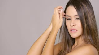 Gorgeous woman with sultry expression using hands to tie up her long brown hair over gray with copy space