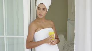 Gorgeous woman wrapped in towel outside with glass of orange juice while leaning against door