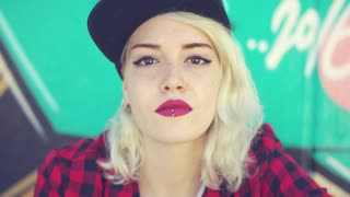 Gorgeous young blond woman with a pierced lip wearing a trendy baseball cap and crimson lipstick posing for the camera in front of colorful graffiti