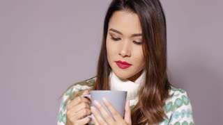 Gorgeous young woman enjoying a large mug of hot coffee or tea blowing on the surface of the liquid as she savors the aroma close up on grey.