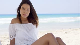 Gorgeous young woman relaxing on the beach sitting under the shade of an umbrella in a trendy white summer top looking at the camera