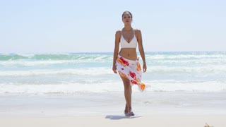 Gorgeous young woman walking along a beach in a bikini and colorful sarong at the waters edge on a summer day