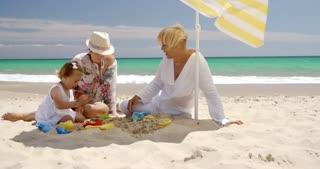 Grandma  Mom and Little Girl Playing at Beach Sand