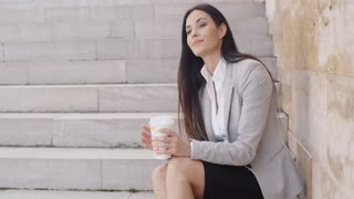 Grinning woman on stairs drinking coffee