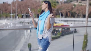 Grinning woman using phone on overpass