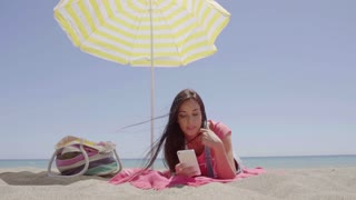 Ground level view of woman using phone at beach