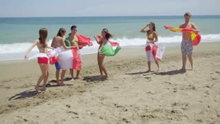 Group of Friends in Swim Suits with Flags at Beach