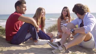 Group of friends sitting and chatting on the beach