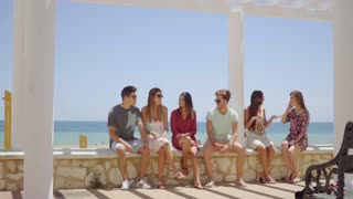 Group of friends sitting on stone wall near beach