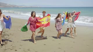 Group of Friends with Flags Walking on Sunny Beach